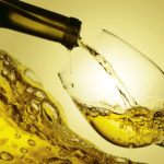 White wine being poured into a wineglass, isolated on white